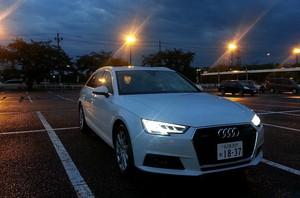 夜間の駐車場でヘッドライトを光らせるAudi アウディA4アバント2.0 TFSIクワトロの写真